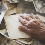 hand resting on old letters and photographs